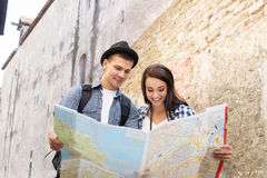 Tourists exploring the map on old baroque street Stock Photos