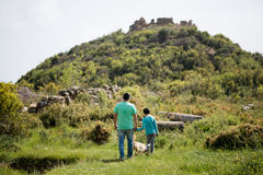 Tourists exploring natural and historical site. Adult and child wearing clothing of bright colors exploring natural and historical site with remains of Antiochia Royalty Free Stock Images