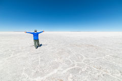 Tourists exploring the world famous Uyuni Salt Flat, among the most important travel destination in the Bolivian Andes. Wide angle. View, clear blue sky Royalty Free Stock Image