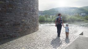 Tourists, father and son together walking along the river embankment royalty free stock images
