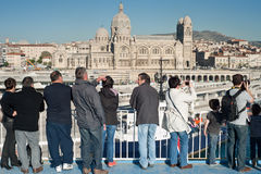 Tourists on a ferry in Marseille. Tourists on a ferry look at the view and take pictures of the Cathedral in Marseille on May 3rd, 2013. The Roman Catholic Royalty Free Stock Photo