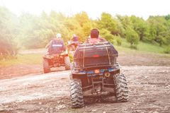 Tourists on a few quad bikes ride on rough terrain on a sunny day in the spring. Toned photo.  stock image