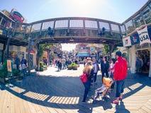 Tourists on Fisherman`s Wharf, Pier 39 under wooden bridge Royalty Free Stock Photos