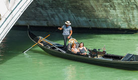 Tourists float in gondola on canal in Venice Stock Photos