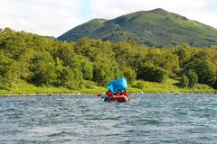 Tourists float on the river with a blue tent in the form of a sail stock photography