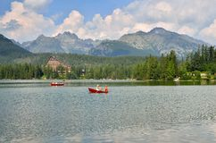Tourists floating boats in Slovak Mountains. STRBSKE PLESO, SLOVAKIA - JULY 4, 2016: Tourists floating boats on the Strbske Pleso lake in High Tatra Mountains Royalty Free Stock Photos