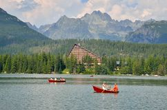 Tourists floating boats in Slovak Mountains. STRBSKE PLESO, SLOVAKIA - JULY 4, 2016: Tourists floating boats on the Strbske Pleso lake in High Tatra Mountains Stock Photography