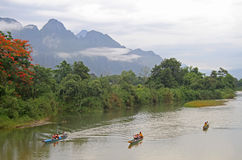 Tourists are floating in canoes nearly Vang Vieng. Vang Vieng, Lao - May 17, 2015 tourists are floating in canoes nearly Vang Vieng, Lao royalty free stock photo