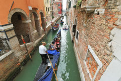Tourists floating in gondola in canal, Venice Stock Photos