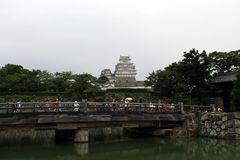 Tourists flocking to enter Himeji Castle, some are waiting on th. E bridge on a cloudy royalty free stock image