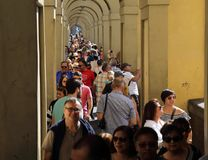 Tourists in Florence, Italy. Florence, Italy - September 23, 2017: Tourists walk under the arches outside the Uffizi Gallery in Florence, Italy on September 23 Royalty Free Stock Photo