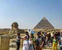 Tourists following a tour guide at Giza. Giza, Egypt: Tourists following a tour guide at Giza in Egypt Stock Photo