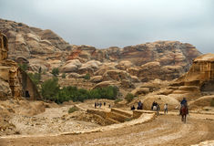 Tourists on foot and on horseback visiting the Petra in Jordan Royalty Free Stock Photo