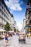 Tourists form all over the World walks among one of the main streets, Kartner Strasse in Vienna, Austria. Stock Image