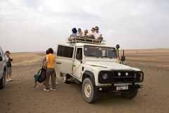 Tourists on the Four-wheel drive. Inn the flat desert and ready to go among the dunes of Erg Chebbi, Morocco. Erg Chebbi is one of Morocco's two Saharan ergs Royalty Free Stock Photos