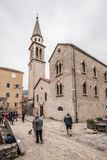 Tourists in front of Church of St Ivan. Tourists walking in the courtyard to the bell tower of the Church of St Ivan, Budva, old town, Montenegro royalty free stock images