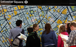 Tourists in front of London map. Some tourists in front of a big map of London in the central Leicester square. Over 26 million tourists visit London every year royalty free stock image