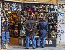 Tourists in Front of a Masks Shop in Venice. Venice,Italy- February 18,2012: Image of a couple of tourists in front of a shop full of traditional masks and Royalty Free Stock Photo