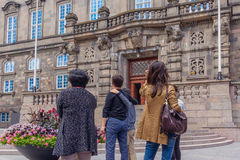 Tourists in front of the national parliament in Copenhagen. Asian tourists standing in front of danish parliament Royalty Free Stock Image