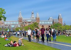 Tourists in front of the Rijksmuseum  State museum , Amsterdam. Amsterdam, North Holland, The Netherlands - May 20 2018:  tourists on the grass in front of the royalty free stock images