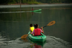 Tourists fun canoeing in Cheow Larn Lake (Ratchaprapa Dam). SURATTHANI,THAILAND-APRIL 6 : Traveler paddle canoeing in fun and happiness on Cheow Larn lake (Khao Stock Photography