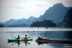 Tourists fun canoeing in Cheow Larn Lake (Ratchaprapa Dam). Stock Images