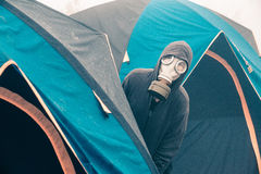 Tourists gas mask out of tents. Stock Photography