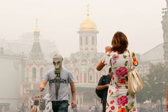 Tourists in a gas mask at the Red Square. Tourists in a gas mask to protect from the high concentration of carbon monoxide caused by smoke from the forest fires Royalty Free Stock Photography