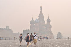 Tourists in gas mask on Red Square under the smog stock images