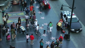 Tourists gather around a street performer in Hollywood stock footage
