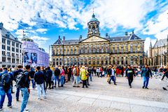 Tourists gathering at the Dam square the center of Amsterdam with the Royal Palace on the background. Amsterdam, the Netherlands - Sept 28, 2018: Tourists stock image