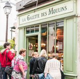 Tourists gaze at baked goods through a Paris bakery window. Paris, France, Sept 5, 2015: Tourists gaze through the windows of a traditional French bakery Royalty Free Stock Image