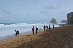 Tourists on Gibson Steps beach at Campbell National Park in Victoria Australia. Landscape view of sea cliffs with unrecognizable people walking on a Gibson Steps stock photography