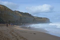 Tourists on Gibson Steps beach at Campbell National Park in Victoria Australia. Landscape view of sea cliffs with unrecognizable people walking on a Gibson Steps royalty free stock photo