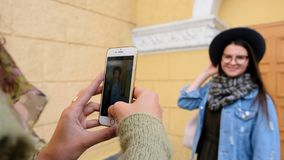 Tourists, girlfriends taking photo with smartphone camera in city close up. Two best friends girls taking photo with smartphone camera in city stock video footage