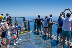 Tourists at the glass platform at the highest european cliff Cab. O Girao, Madeira, Portugal. People are enjoying stunning Atlantic ocean view and making photos royalty free stock photo