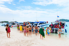 Tourists go on board the speed boat on the beach Stock Images