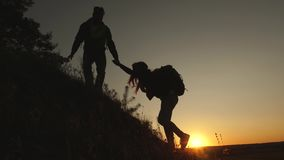 Tourists go down from the goy in the sunset, holding hands. male traveler holds the hand of a female traveler going down. Tourists go down from the goy in the stock footage
