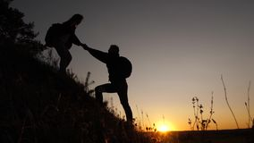 Tourists go down from the goy in the sunset, holding hands. male traveler holds the hand of a female traveler going down. Tourists go down from the goy in the stock video footage