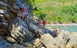 Tourists go on huge rocks from Mogren beach to cliff with view point, Budva, Montenegro royalty free stock image