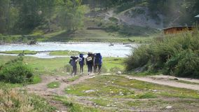 Tourists go trekking in the mountains near mountain river stock video