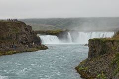 Tourists at The Godafoss Icelandic: waterfall of the gods which is a famous waterfall in Iceland. The breathtaking landscape of