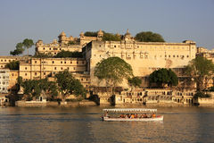 Tourists going in motorboat in front of City Palace complex, Udaipur, India Stock Image