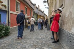 Tourists in the Golden Lane, Prague Castle. Tourists from all over the world visiting the Golden Lane in Prague Castle in the Czech Republic and taking pictures stock image