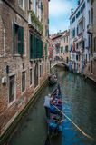 Tourists on a gondola on the canal of Venice royalty free stock photo