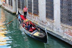 Tourists in gondola on canal in Venice Stock Photography