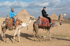 Tourists at the Great Pyramids of Giza. Male and female tourists on camels in desert with Great Pyramids of Giza in background, Egypt royalty free stock photo