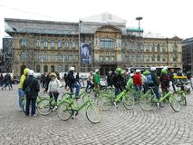GREEN BICYCLES, HELSINKI, FINLAND. Helsinki, Finland - May 1, 2015: Group of tourists with green bicycles waiting to go on a city tour in Helsinki, Finland Royalty Free Stock Image