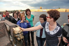 Tourists and guests of St. Petersburg have the mystical characters of the urban fabulous Gryphon on the river Neva embankment. Royalty Free Stock Images