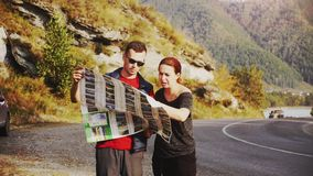 Tourists are guided by the terrain with a map. Pretty couple stand in amazing picturesque place amidst the mountains stock footage